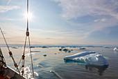 Ship sailing past melting ice on Atlantic Ocean Greenland