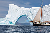 Ship sailing past majestic iceberg arch on ocean Greenland