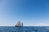 Ship sailing past melting polar ice on blue
