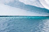 Turquoise blue ocean water below iceberg Greenland