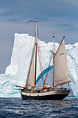 Ship sailing past iceberg on Atlantic Ocean Greenland