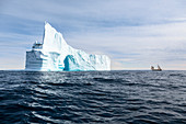 Majestic iceberg arch over tranquil blue