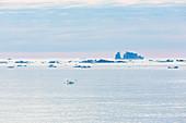 Melting icebergs on vast tranquil Atlantic Ocean Greenland
