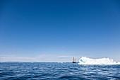 Ship sailing behind iceberg on blue