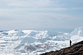 Man standing on cliff overlooking glacial ice melt