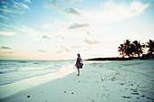 Woman in sun dress on tropical ocean beach Mexico