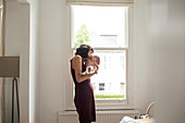 Mother kissing newborn baby son in window