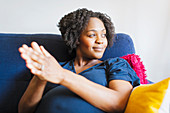 Happy pregnant woman rubbing hands together on sofa