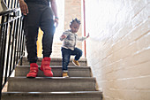 Father and toddler son descending steps