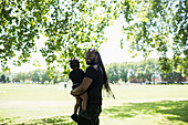 Father with long braids carrying son in park