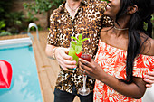 Young couple drinking cocktails at poolside
