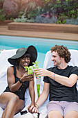 Happy multiethnic couple drinking cocktails at poolside