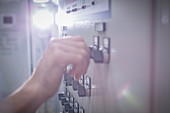 Close up hand adjusting knob at control panel in factory