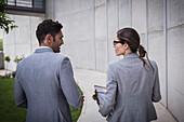 Businessman and businesswoman talking on sidewalk