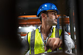 Male worker driving forklift in factory