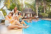 Friends splashing at sunny summer poolside