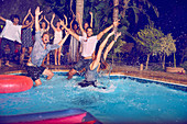 Exuberant young friends jumping into swimming pool