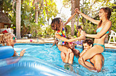 Young couples playing chicken fight in summer swimming pool