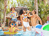 Friends drinking and playing in sunny summer swimming pool