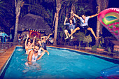 Young men friends jumping into swimming pool at night