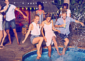 Playful young friends jumping into swimming pool