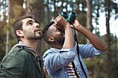 Young men with binoculars bird watching in woods