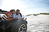 Young couple using digital tablet in jeep on sunny beach