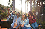 Young friends taking selfie at jeep in woods