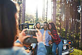 Young woman photographing friends at jeep in woods
