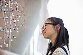 Pensive, curious girl student examining molecular structure