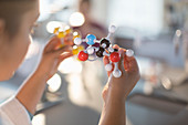 Curious girl student holding molecule model in classroom