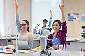 Eager students raising hands in science laboratory classroom