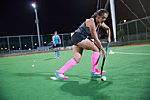 Young female field hockey player playing on field at night