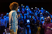 Audience with smart phone flashlights listening to speaker