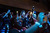Enthusiastic audience using camera phones in dark auditorium