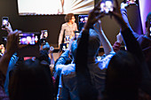 Audience with camera phones photographing speaker on stage