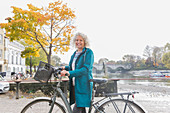 Portrait smiling senior woman bike riding along autumn river