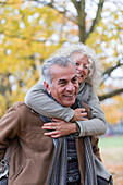 Playful, smiling senior couple piggybacking in autumn park