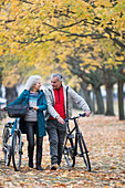 Senior couple walking bicycles among trees and leaves