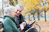 Couple reading newspaper and drinking coffee on bench