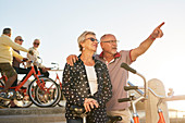 Active senior couple tourists with bicycles looking at view