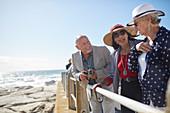 Active senior tourist friends at sunny ocean overlook