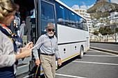 Active senior man tourist disembarking tour bus