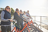 Active senior tourist friends on bicycles on sunny boardwalk