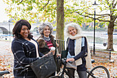 Active senior women friends with coffee and bicycles