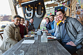 Portrait smiling friends eating at restaurant outdoor patio