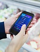 Close up woman using digital shopping list on smart phone