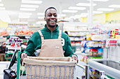 Smiling, confident male grocer working in supermarket