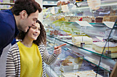 Couple looking at desserts in bakery display case