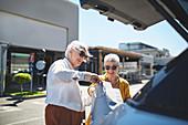 Senior women friends loading shopping bags into back of car